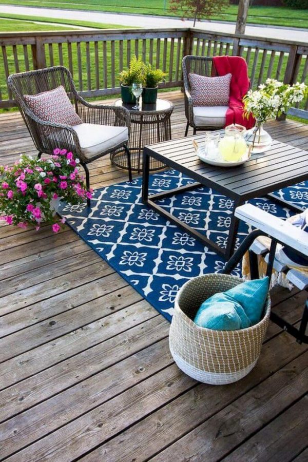a colorful eclectic deck with a bright rug wicker and wooden furniture